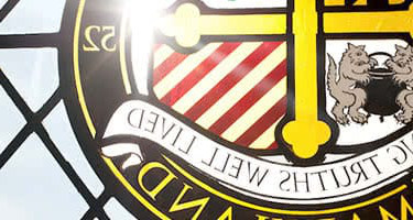 The sun shining through a stained glass Loyola seal